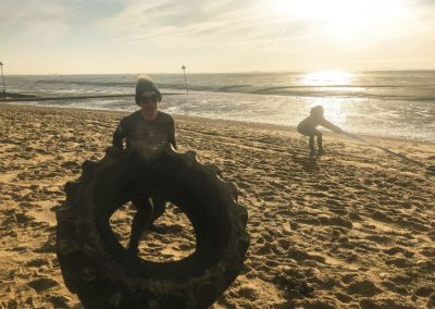 Rebel Health training on beach with tyres